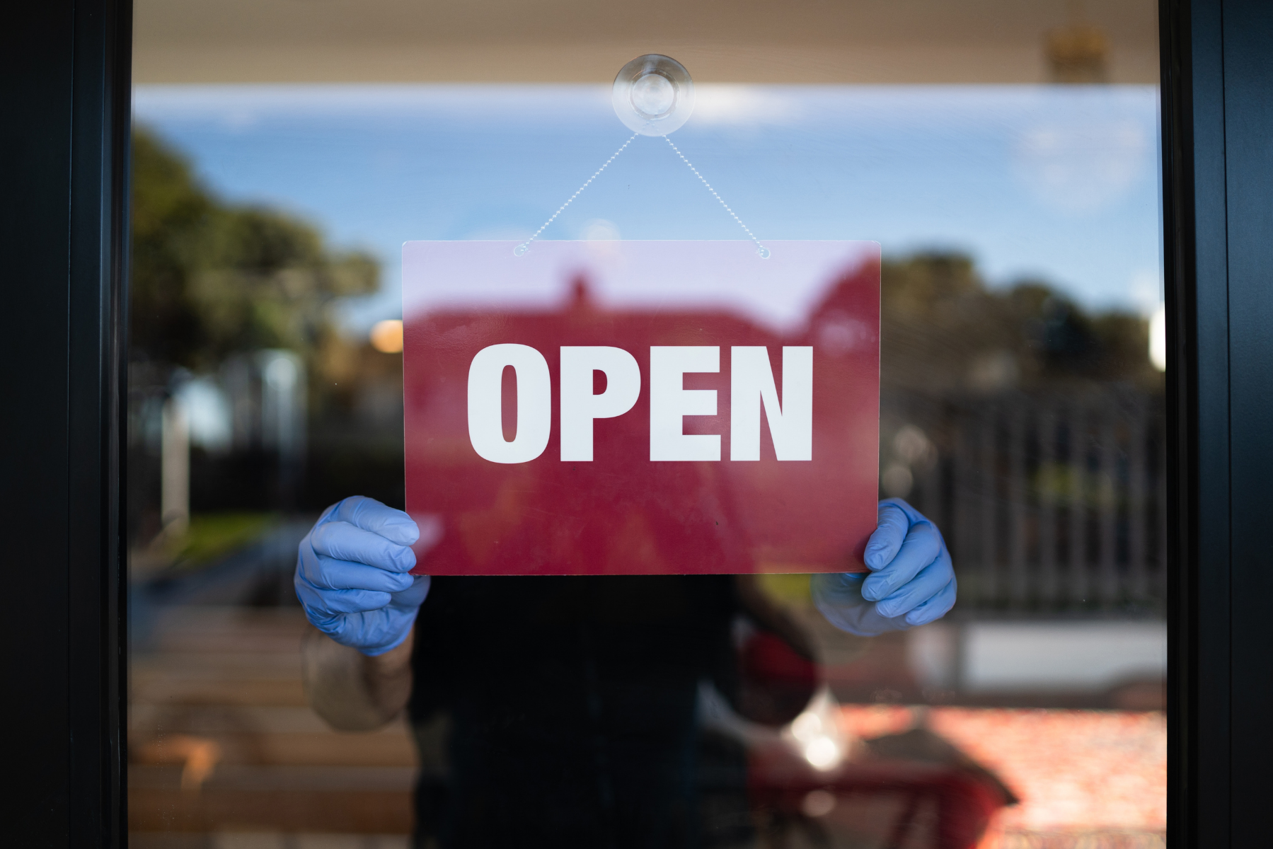 Person holding an open sign up to a transparent door