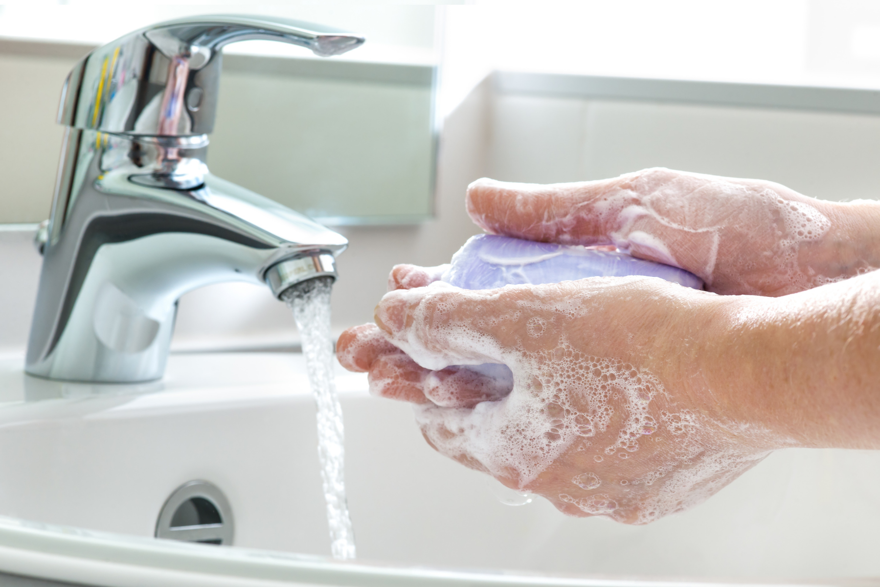 Person cleaning their hands in a sink with hand soap