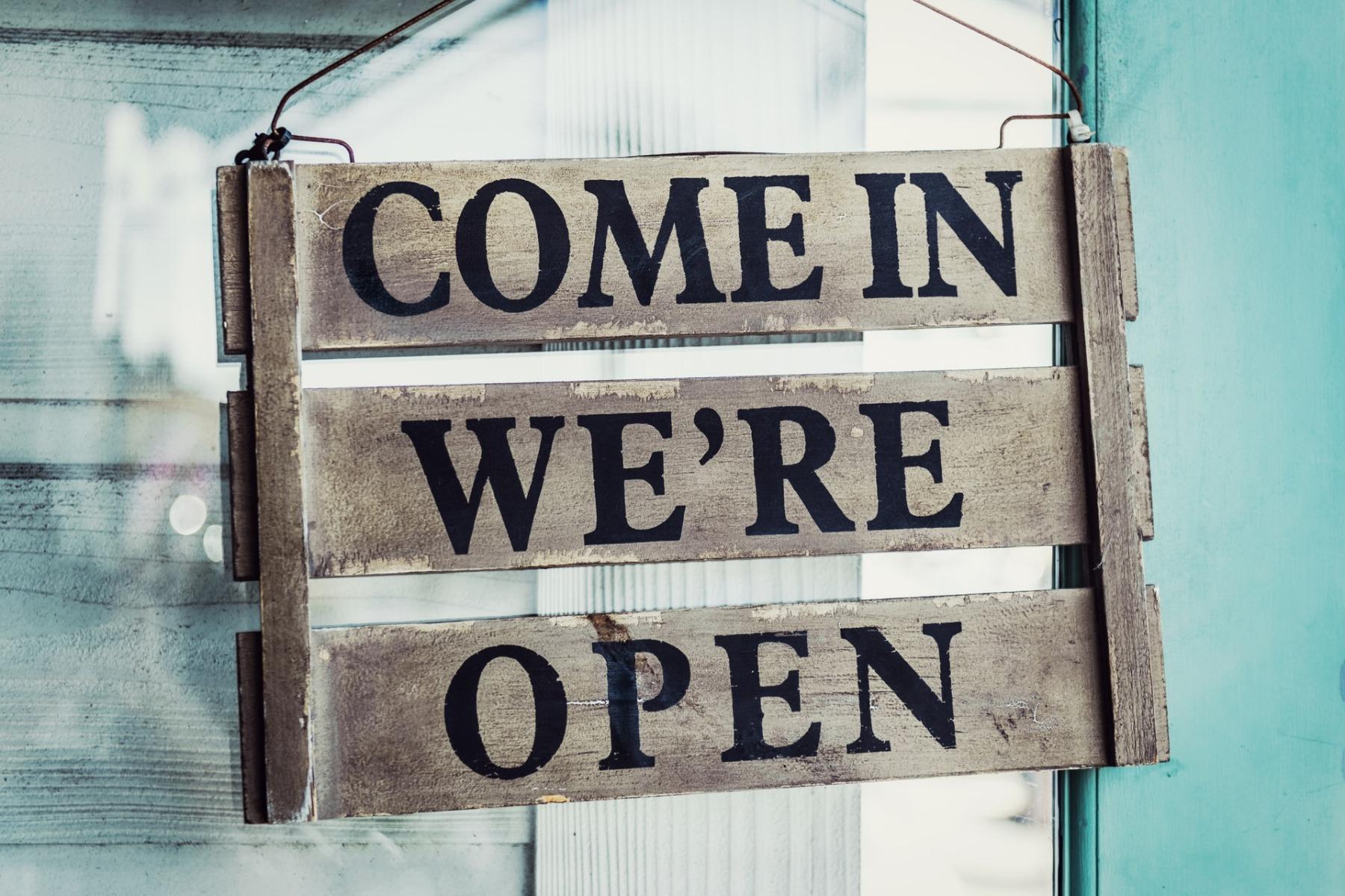 """come in we're open"" wooden sign hanging from a door"