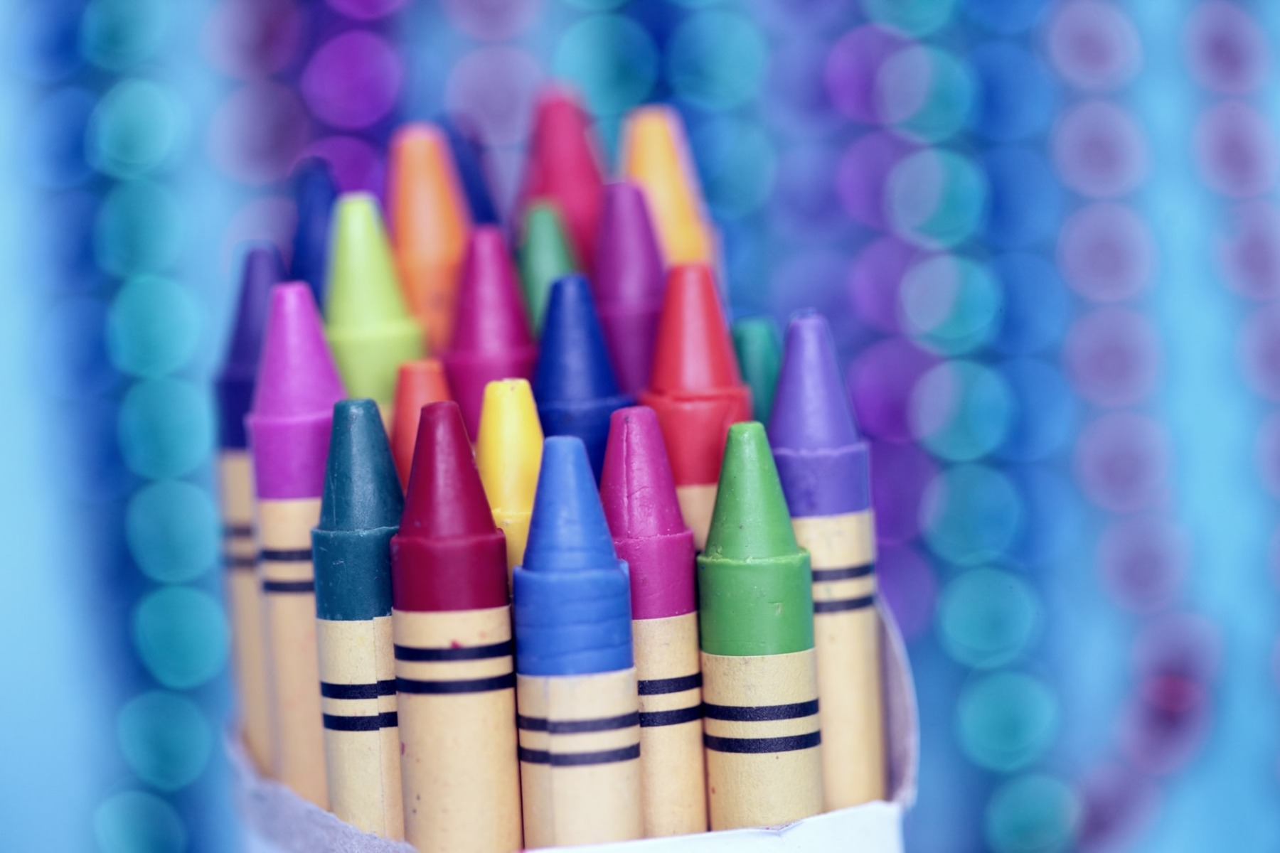 A box full of crayons nfront of a purple background