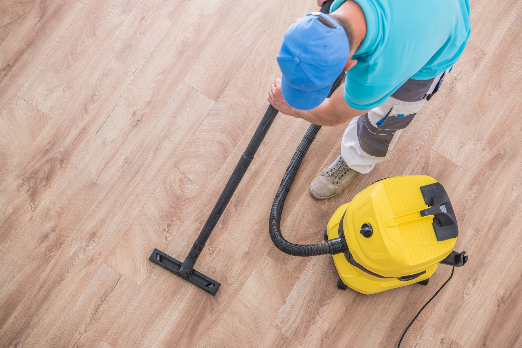 Man with a blue hat hoovering the floor with a Victor V9 Vacuum Cleaner
